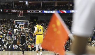 """In this Thursday, Oct. 10, 2019, photo, Brooklyn Nets' Theo Pinson, left, drives against Los Angeles Lakers' Danny Green, right, near a Chinese national flag during a preseason NBA game at the Mercedes Benz Arena in Shanghai, China. When Houston Rocket's general manager Daryl Morey tweeted last week in support of anti-government protests in Hong Kong, everything changed for NBA fans in China. A new chant flooded Chinese sports forums: """"I can live without basketball, but I can't live without my motherland."""" (AP Photo, File)"""
