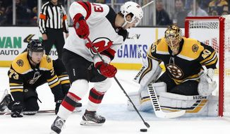 New Jersey Devils' Nico Hischier (13) tries to shoot against Boston Bruins goalie Tuukka Rask (40) during the first period of an NHL hockey game in Boston, Saturday, Oct. 12, 2019. (AP Photo/Michael Dwyer)