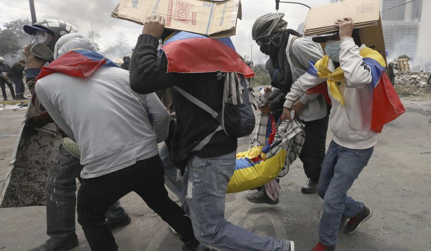 Anti-government demonstrators carry a wounded comrade away from the action during clashes with police in Quito, Ecuador, Saturday, Oct. 12, 2019. Protests, which began when President Lenin Moreno's decision to cut subsidies led to a sharp increase in fuel prices, have persisted for days. (AP Photo/Fernando Vergara)