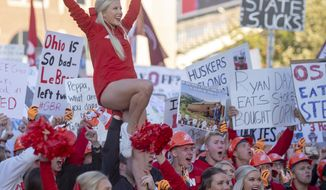 This Sept. 28, 2019 photo shows a Husker cheerleader is held in the air during College Gameday outside of Memorial Stadium in Lincoln, Neb.  The group is practicing and perfecting the skills to ensure it puts on an entertaining and, more importantly, safe performance. (Emily Haney/Lincoln Journal Star via AP)