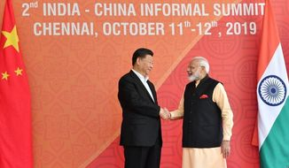 In this handout photo provided by the Indian Prime Minister's Office, Chinese President Xi Jinping and Indian Prime Minister Narendra Modi shake hands in Mamallapuram, India. Xi met with Modi at a time of tensions over Beijing's support for Pakistan in opposing India's downgrading of Kashmir's semi-autonomy and continuing restrictions on the disputed region. (Indian Prime Minister's Office via AP)