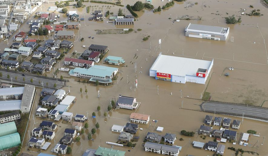 Houses are submerged in muddy waters in Sukagawa, Fukushima prefecture, as Typhoon Hagibis hits the area, northern Japan, Sunday, Oct. 13, 2019. Rescue efforts for people stranded in flooded areas are in full force after a powerful typhoon dashed heavy rainfall and winds through a widespread area of Japan, including Tokyo.(Takuya Inaba/Kyodo News via AP)