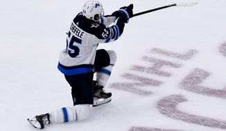 Winnipeg Jets center Mark Scheifele (55) reacts after scoring the winning goal during overtime of an NHL hockey game against the Chicago Blackhawks, Saturday, Oct. 12, 2019, in Chicago. (AP Photo/Matt Marton)