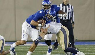 Tulsa quarterback Zack Smith (11) is taken down by Navy's Diego Fagot (54) during an NCAA college football game, Saturday, Oct. 12, 2019, in Tulsa, Okla. (Stephen Pingry/Tulsa World via AP)