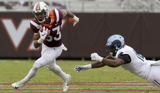 Virginia Tech running back Deshawn McClease (33) escapes Rhode Island defender Branyan Javier- Castillo (16) in the first half of an NCAA college football game in Blacksburg Va., Saturday, Oct. 12 2019. (Matt Gentry/The Roanoke Times via AP)