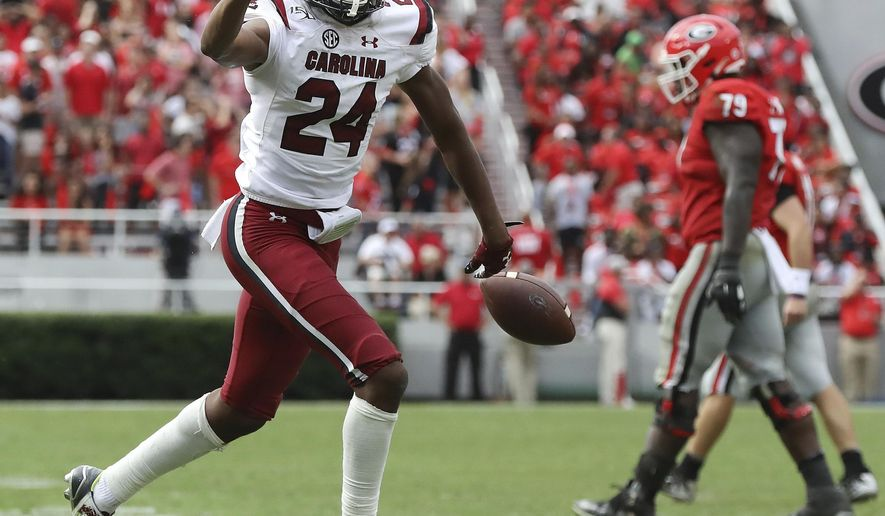 South Carolina defensive back Israel Mukuamu holds up three fingers after intercepting a pass during the first overtime period of an NCAA college football game, Saturday, Oct., 12, 2019, in Athens, Ga. (Curtis Compton/Atlanta Journal-Constitution via AP)
