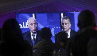 CORRECTS POSITION - People watch a televised debate between presidential candidates Kais Saied, left, and Nabil Karoui, on the last day of campaigning before the second round of the presidential elections, in Tunis, Tunisia, Friday, Oct. 11, 2019. (AP Photo/Mosa'ab Elshamy)