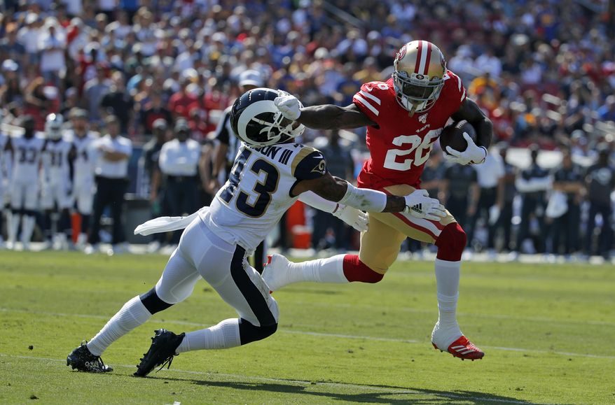 San Francisco 49ers running back Tevin Coleman (26) runs around Los Angeles Rams strong safety John Johnson (43) to score a touchdown during the first half of an NFL football game Sunday, Oct. 13, 2019, in Los Angeles. (AP Photo/John Locher )