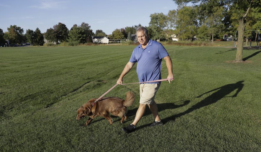 Mark Stenske walks his dog, Leo, as he discusses the impeachment inquiry into President Donald Trump while walking in a park, Wednesday, Oct. 9, 2019, in Fishers, Ind. (AP Photo/Darron Cummings)