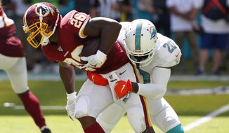 Miami Dolphins free safety Reshad Jones (20) tackles Washington Redskins running back Adrian Peterson (26)during the first half at an NFL football game, Sunday, Oct. 13, 2019, in Miami Gardens, Fla. (AP Photo/Wilfredo Lee)