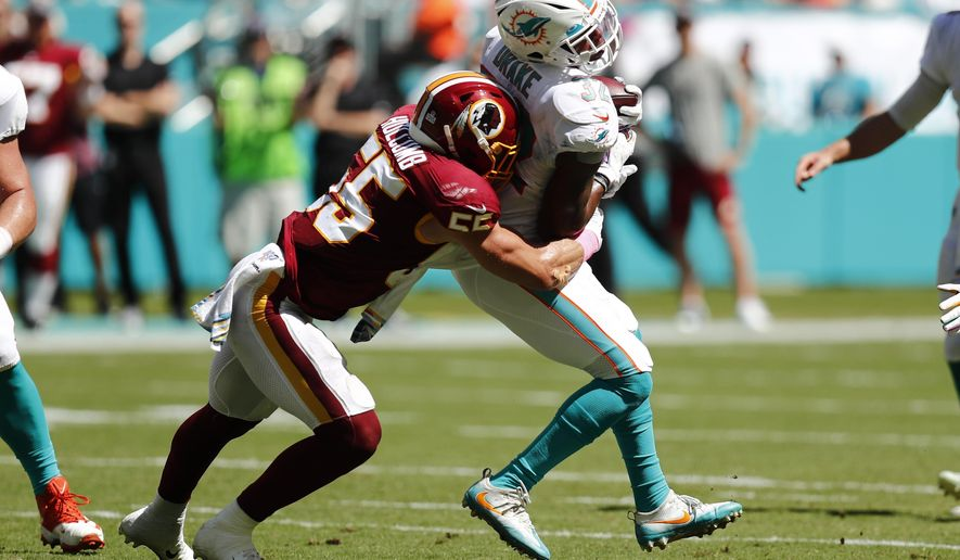 Washington Redskins linebacker Cole Holcomb (55) tackles Miami Dolphins running back Kenyan Drake (32), during the first half at an NFL football game, Sunday, Oct. 13, 2019, in Miami Gardens, Fla. (AP Photo/Brynn Anderson) ** FILE **