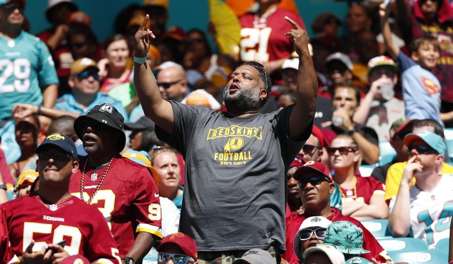 A Washington Redskins fan cheers the team, during the first half at an NFL football game against the Miami Dolphins, Sunday, Oct. 13, 2019, in Miami Gardens, Fla. (AP Photo/Wilfredo Lee)