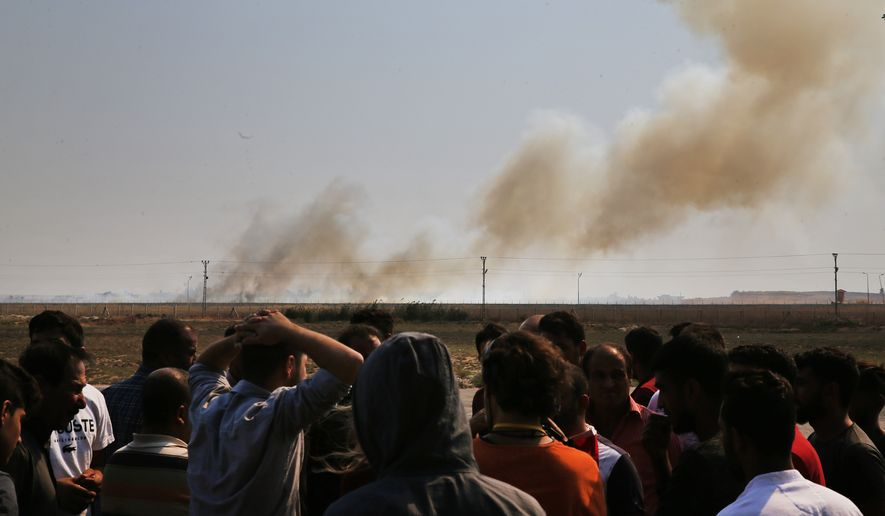 People watch from Akcakale, Sanliurfa province, southeastern Turkey, as smoke billows from fires on targets in Tel Abyad, Syria, caused by bombardment by Turkish forces, Sunday, Oct. 13, 2019. The United Nations says at least 130,000 people have been displaced by the fighting in northeastern Syria with many more likely on the move as a Turkish offensive in the area enters its fifth day.(AP Photo/Lefteris Pitarakis)