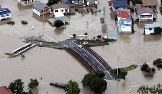 Cars are stranded on a road as the city is submerged in muddy waters after an embankment of the Chikuma River broke, in Nagano, central Japan, Sunday, Oct. 13, 2019. Rescue efforts for people stranded in flooded areas are in full force after a powerful typhoon dashed heavy rainfall and winds through a widespread area of Japan, including Tokyo. (Yohei Kanasashi/Kyodo News via AP)