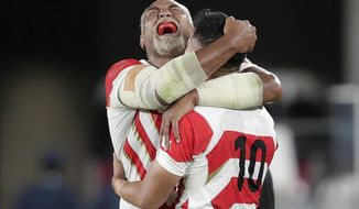 Japan's Isileli Nakajima, left, celebrates with Yu Tamura after the Rugby World Cup Pool A game at International Stadium against Scotland in Yokohama, Japan, Sunday, Oct. 13, 2019. Japan won 28-21. (AP Photo/Jae Hong)