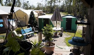 In this Thursday, Oct. 10, 2019 photo, Shelly Summers' backyard  has become a refuge for those left homeless from Hurricane Michael near Panama City, Fla. It has been a year since Hurricane Michael roared across the eastern Florida Panhandle, a Category 5 storm that laid waste to the coastline and ravaged areas far inland. Yet in rural Bay County, amid forests of snapped trees and the more-than-occasional home still roofed with a blue tarp. (Joshua Boucher/News Herald via AP)