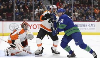 Vancouver Canucks' Jake Virtanen (18) fights for the puck with Philadelphia Flyers' Matt Niskanen (15) as Flyers goalie Carter Hart (79) watches during the first period of an NHL hockey game Saturday, Oct. 12, 2019, in Vancouver, British Columbia. (Ben Nelms/The Canadian Press via AP)