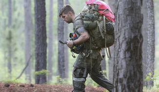 A soldier from the U.S. Army John F. Kennedy Special Warfare Center and School checks a compass while completing a land navigation course during Special Forces Assessment and Selection near Hoffman, N.C., May 7, 2019. Commanders are making big changes to the grueling course that soldiers must pass to join the elite Special Forces. The goal is to meet evolving national security threats and to shift from a culture that weeds out struggling soldiers to one that trains them to do better. (Ken Kassens/U.S. Army via AP)