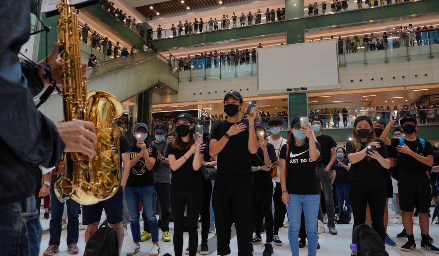 Protestors wearing masks in defiance of a recently imposed ban on face coverings perform at a shopping mall in Hong Kong, Sunday, Oct.13, 2019. The semi-autonomous Chinese city is in its fifth month of a movement that initially began in response to a now-withdrawn extradition bill that would have allowed Hong Kong residents to be tried for crimes in mainland China. The protests have since ballooned to encompass broader demands for electoral reforms and an inquiry into alleged police abuse. (AP Photo/Vincent Yu)