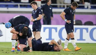 Scotland players react following their 28-21 loss to Japan in their Rugby World Cup Pool A game at International Stadium in Yokohama, Japan, Sunday, Oct. 13, 2019. (AP Photo/Christophe Ena)