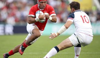 Tonga's Siale Piutau, left, runs at United States' AJ MacGinty during the Rugby World Cup Pool C game at Hanazono Rugby Stadium between USA and Tonga in Osaka, Japan, Sunday, Oct. 13, 2019. (Kyodo News via AP)