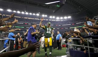Green Bay Packers' Aaron Rodgers acknowledges fans as he walks off the field after the team's NFL football game against the Dallas Cowboys in Arlington, Texas, Sunday, Oct. 6, 2019. (AP Photo/Roger Steinman)