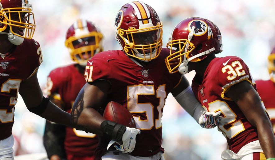 Washington Redskins linebacker Shaun Dion Hamilton (51) is congratulated after intercepting a pass, during the second half at an NFL football game against the Miami Dolphins, Sunday, Oct. 13, 2019, in Miami Gardens, Fla. (AP Photo/Brynn Anderson)