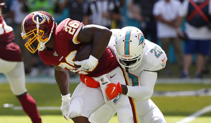 Miami Dolphins free safety Reshad Jones (20) tackles Washington Redskins running back Adrian Peterson (26)during the first half at an NFL football game, Sunday, Oct. 13, 2019, in Miami Gardens, Fla. (AP Photo/Wilfredo Lee) **FILE**