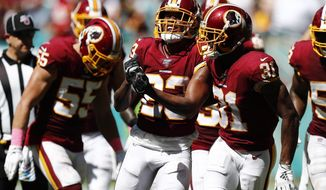 Washington Redskins cornerback Quinton Dunbar (23) celebrates after intercepting a pass, during the first half at an NFL football game against the Miami Dolphins, Sunday, Oct. 13, 2019, in Miami Gardens, Fla. (AP Photo/Brynn Anderson)