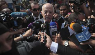 Tunisian independent law professor and presidential candidate Kais Saied speaks to journalists after casting his ballot in a polling station during the second round of the presidential election, in Tunis, Tunisia, Sunday, Oct. 13, 2019. Tunisians are voting for president, choosing between a law professor and populist tycoon. (AP Photo/Mosa'ab Elshamy)