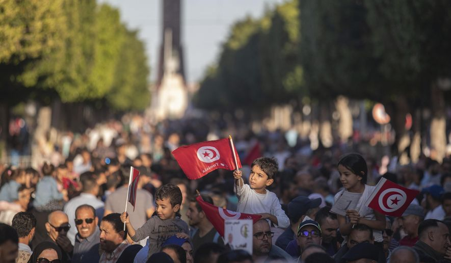 Children wave Tunisian flags as supporters of independent Tunisian Presidential candidate Kais Saied attend a rally on the last day of campaigning before the second round of the presidential elections, in Tunis, Tunisia, Friday, Oct. 11, 2019. (AP Photo/Mosa'ab Elshamy)