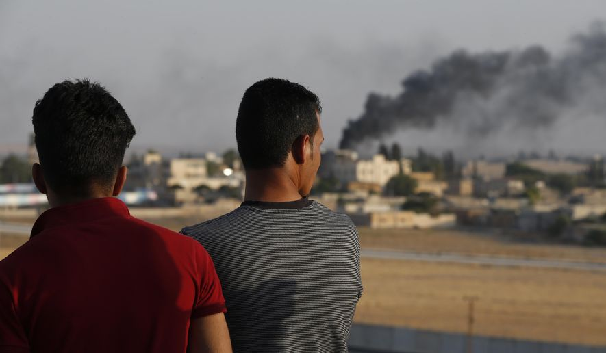 People standing on a rooftop in Akcakale, Sanliurfa province, southeastern Turkey, at the border with Syria, watch as in the background smoke billows from fires caused by Turkish bombardment in Tal Abyad, Syria, Sunday, Oct. 13, 2019.  Turkey's official Anadolu news agency says Turkey-backed Syrian forces have advanced into the center of a Syrian border town, Tal Abyad, on the fifth day of the Turkey's military offensive against Kurdish fighters in Syria. (AP Photo/Lefteris Pitarakis)