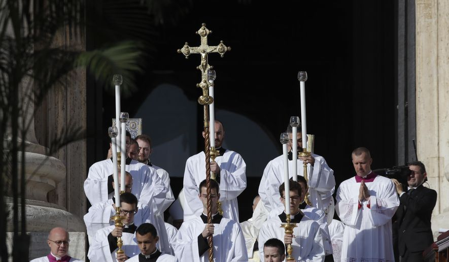 Priests hold candles and a crucifix during a canonization Mass in St. Peter's Square at the Vatican, Sunday, Oct. 13, 2019. Pope Francis canonizes Cardinal John Henry Newman, the 19th century Anglican convert who became an immensely influential thinker in both Anglican and Catholic churches, and four other women. (AP Photo/Alessandra Tarantino)