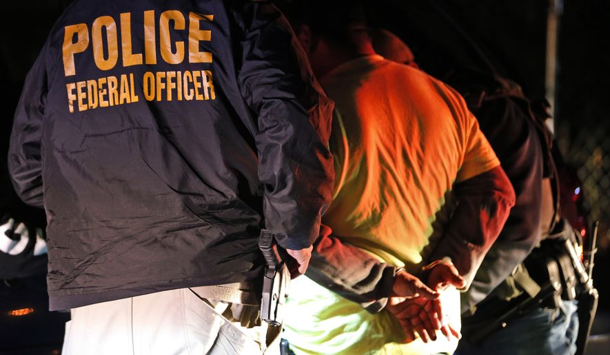 In this Oct. 22, 2018, file photo, U.S. Immigration and Customs Enforcement agents detain a person during a raid in Richmond, Va. (AP Photo/Steve Helber, File) **FILE**