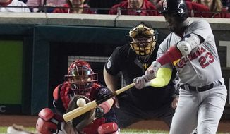 St. Louis Cardinals' Marcell Ozuna hits a double during the second inning of Game 3 of the baseball National League Championship Series against the Washington Nationals Monday, Oct. 14, 2019, in Washington. (AP Photo/Alex Brandon)