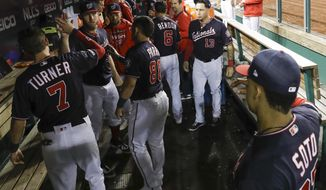 Washington Nationals starting pitcher Stephen Strasburg is congratulated by teammates after getting St. Louis Cardinals' Dexter Fowler to strike out during the seventh inning of Game 3 of the baseball National League Championship Series Monday, Oct. 14, 2019, in Washington. (AP Photo/Jeff Roberson)