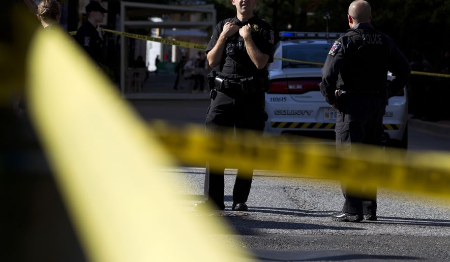 Montgomery County police officers block the intersection outside a  parking garage is seen, where a police officer was shot, in downtown Silver Spring, Md., Monday, Oct. 14, 2019. (AP Photo/Jose Luis Magana)