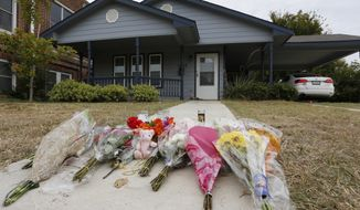 Flowers lie on the sidewalk in front of the house in Fort Worth, Texas, Monday, Oct. 14, 2019. A white Fort Worth police officer who shot and killed a black woman through a back window of her home while responding to a call about an open front door acted without justification and resigned Monday before he could be fired, the police chief said. (David Kent/Star-Telegram via AP)