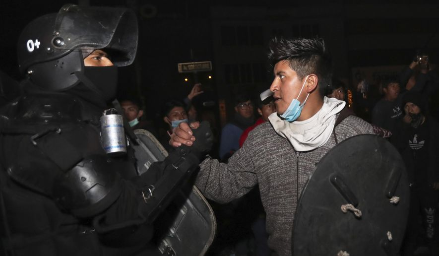 One of the protesters shakes hands with a security officer as they celebrate the announcement that the government cancelled an austerity package that triggered violent protests, in Quito, Ecuador, Sunday, Oct. 13, 2019. Ecuadorian President Lenin Moreno and leaders of the country's indigenous peoples have struck a deal to cancel the disputed austerity package and end nearly two weeks of protests that have paralyzed the economy and left several people dead. (AP Photo/Dolores Ochoa)