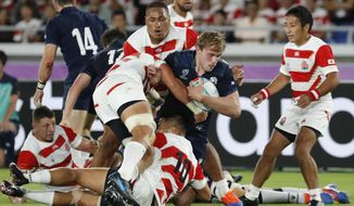 Scotland's Jonny Gray is tacked by Japan's defense during the Rugby World Cup Pool A game at International Stadium between Japan and Scotland in Yokohama, Japan, Sunday, Oct. 13, 2019. (AP Photo/Eugene Hoshiko)