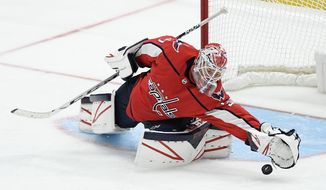 Washington Capitals goaltender Ilya Samsonov (30), of Russia, reaches for the puck during the third period of an NHL hockey game against the Colorado Avalanche, Monday, Oct. 14, 2019, in Washington. (AP Photo/Nick Wass) ** FILE **
