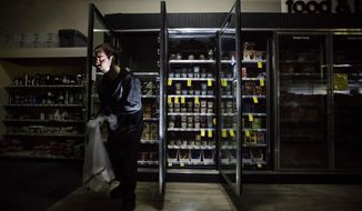 """FILE - In this Oct. 9, 2019, file photo, CVS Pharmacy shift supervisor James Quinn throws out ice cream from darkened freezers as downtown Sonoma, Calif., remains without power. California's utility regulator is issuing a series of sanctions against Pacific Gas and Electric for what it calls """"failures in execution"""" during the largest planned power shut-off in state history to avoid wildfires. (AP Photo/Noah Berger, File)"""