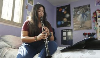 Briana Lopez, a freshman at Lincoln High School and a member of the school's band, practices the clarinet at her home in Lincoln, Calif., Monday, Oct. 14, 2019. California has become the first state to enact a start time for public high schools and middle schools. Gov. Gavin Newsom signed a law Sunday that bans most high schools from starting before 8:30 a.m. and most middle schools from starting before 8 a.m. (AP Photo/Rich Pedroncelli)