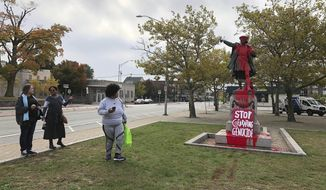 People stop to view red paint covering a statue of Christopher Columbus on Monday, Oct. 14, 2019, in Providence, R.I., after it was vandalized on the day named to honor him as one of the first Europeans to reach the New World. The statue has been the target of vandals on Columbus Day in the past. (AP Photo/Michelle R. Smith)