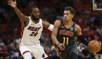 Atlanta Hawks guard Trae Young (11) dribbles against Miami Heat forward Justise Winslow (20) during the first half of an NBA preseason basketball game Monday, Oct. 14, 2019, in Miami. (AP Photo/Brynn Anderson)