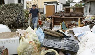A man carries household goods out of a flooded house in Motomiya, Fukushima prefecture, Japan Tuesday, Oct. 15, 2019. Typhoon Hagibis dropped record amounts of rain for a period in some spots, according to meteorological officials, causing more than 20 rivers to overflow. Some of the muddy waters in streets, fields and residential areas have subsided. But many places remained flooded, with homes and surrounding roads covered in mud and littered with broken wooden pieces and debris. (Kyodo News via AP)