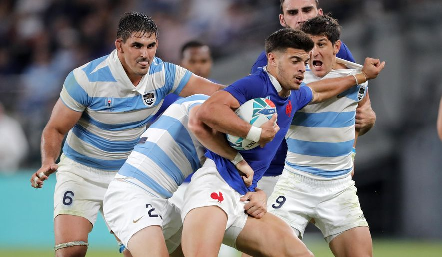 FILE - In this Saturday, Sept. 21, 2019 file photo, France's Romain Ntamack is tackled by Argentinian defenders during the Rugby World Cup Pool C game at Tokyo Stadium between France and Argentina in Tokyo, Japan. Flyhalf Ntamack, is the son of Emile Ntamack who played 46 times for France and is equal fifth on its all-time try scorers' list, is tipped to start Sunday's quarterfinal against Wales, 20 years after his father played the final. (AP Photo/Christophe Ena)