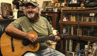 In this undated photo, Kostas Lazarides, 70, plays guitar at his home in Belgrade, Mont. Lazarides, known professionally as Kostas, was being inducted into the Nashville Songwriters Hall of Fame on Monday, Oct. 14, 2019. (Shaylee Ragar/Bozeman Daily Chronicle via AP)