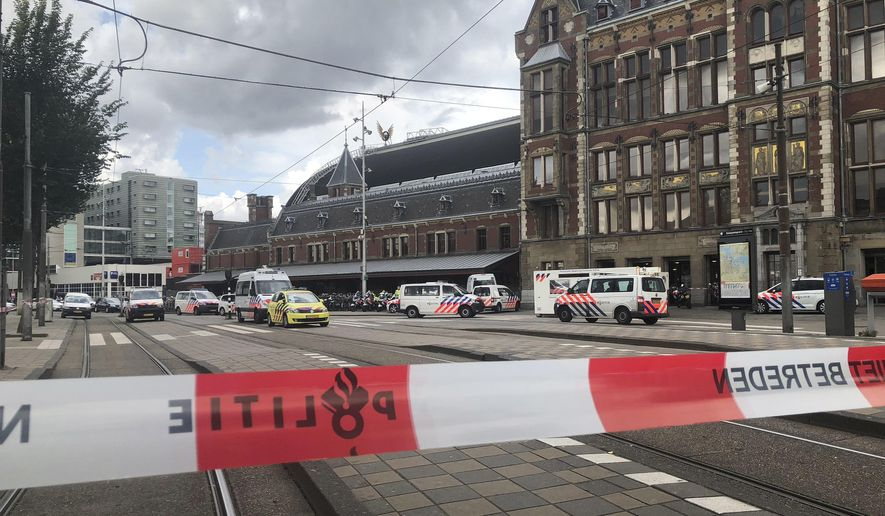 FILE - In this Friday August 31, 2018, image Dutch police officers near the scene of a stabbing attack at central station in Amsterdam, the Netherlands. A Dutch court is expected to deliver its verdict Monday Oct. 14, 2019, in the case against an Afhgan asylum-seeker for stabbing two American tourists at Amsterdam's main railway station. (AP Photo/Aleks Furtula, File)