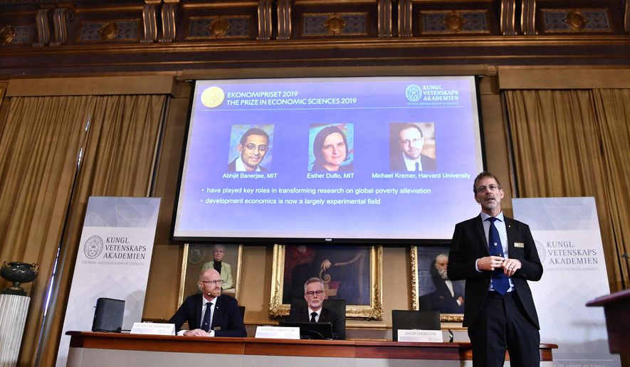 """Goran K Hansson, Secretary General of the Royal Swedish Academy of Sciences, center, and academy members Peter Fredriksson, left, and Jakob Svensson announce the winners of the 2019 Nobel Prize in Economics during a news conference at the Royal Swedish Academy of Sciences in Stockholm, Sweden, Monday Oct. 14, 2019. The Nobel prize in economics has been awarded to Abhijit Banerjee, Esther Duflo and Michael Kremer """"for their experimental approach to alleviating global poverty."""" (Karin Wesslen/TT via AP)"""